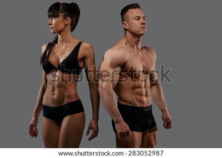 Bodybuilders couple in underwear. Isolated on grey - stock photo