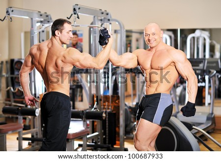 Bodybuilders shake each others hands at the gym after a workout - stock photo