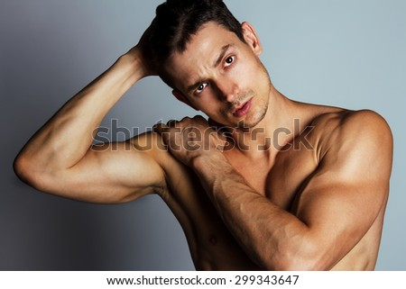 Bodybuilding and body sculpture concept. Handsome muscular male model with perfect body posing over grey background. Close up. Studio shot - stock photo