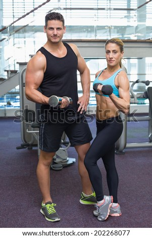 Bodybuilding man and woman holding dumbbells looking at camera at the gym - stock photo