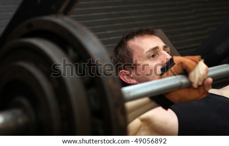 bodybuilding workout in gym. Male lifting free weights training pecks using barbell. - stock photo