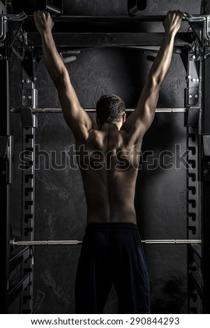 Bodybuilding, Young Athletic Strong Man showing Back Muscles working on Fitness Bar, Strong Contrast with Desaturated Grunge filter - stock photo