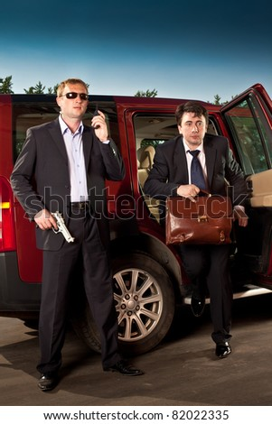 bodyguard and its boss leave the car - stock photo