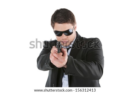 Bodyguard. Confident young man holding gun and aiming camera while standing isolated on white - stock photo