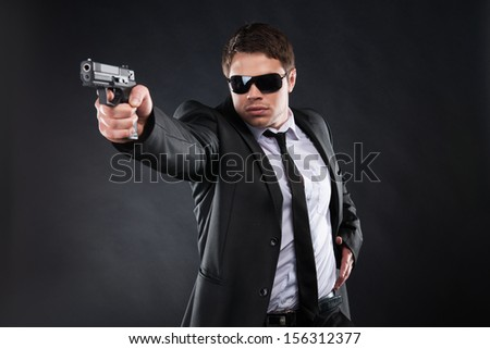 Bodyguard. Confident young man in formalwear holding gun and aiming somewhere while standing against black background - stock photo