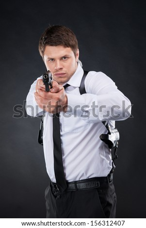 Bodyguard. Confident young man in shirt and tie holding gun and aiming you while standing against black background - stock photo