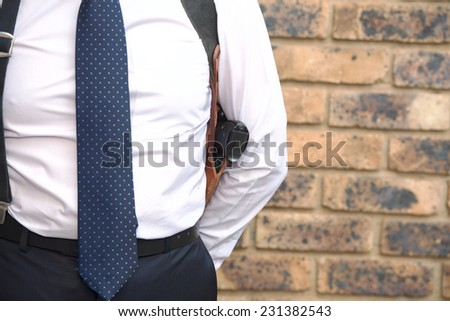 Bodyguard in a white shirt with a tie and a pistol - stock photo