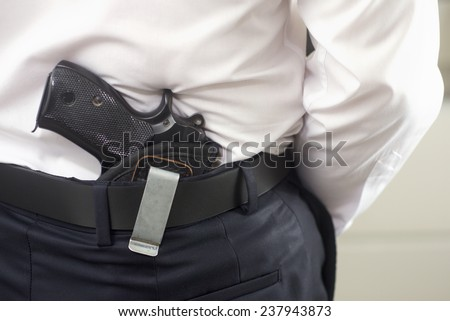 Bodyguard with gun on the front of the door - stock photo