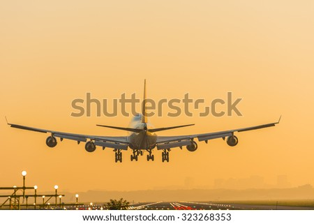 Boeing 747 is almost landed at the runway. Photo taken during a nice sunrise. - stock photo