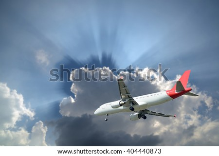 Boeing 737 jet aeroplane landing through gap in sky.,on sun beam and sky-clouds background. - stock photo