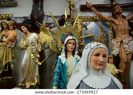 BOGOTA, COLOMBIA - APRIL 24, 2015: A shop in downtown Bogota sells Christian figurines and statues, including angels, Mary, and Jesus hanging on the cross. - stock photo