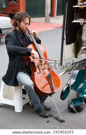 BOGOTA, COLOMBIA - APRIL 06, 2014: An unidentified musician playing cello for money in the streets of Usaquen in Bogota Colombia. Usaquen was declared a national monument in 1987. - stock photo