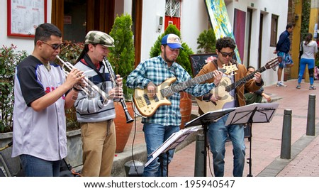 BOGOTA, COLOMBIA - APRIL 06, 2014: Unidentified musical quartet playing for money in the streets of Usaquen in Bogota Colombia. Usaquen was declared a national monument in 1987. - stock photo