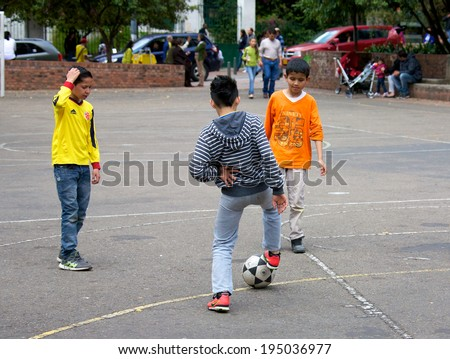 BOGOTA, COLOMBIA - APRIL 06, 2014: Young children playing soccer on pavement in a park in Bogota Colombia.  - stock photo