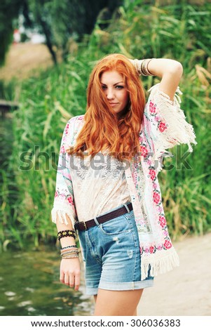 Bohemian fashion girl in kimono and blue denim shorts. Red haired young woman in summer outfit. Portrait of a beautiful girl standing by the river, enjoying a warm summer day in the nature. - stock photo