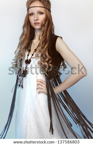 Bohemian woman in spring/summer clothes with beautiful accessories, natural make-up and shiny hairstyle. Perfect long white dress, brown suede jacket and long curly hair. Fashion hippie style. - stock photo