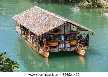 BOHOL, PHILIPPINES - FEBRUARY 21, 2014 : Tourist boat with people on a jungle river. Island Bohol is one of the top tourist destinations in the world. - stock photo