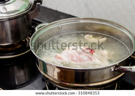 Boil chicken in the pot - stock photo
