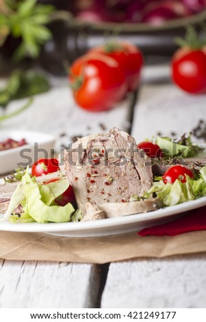 Boiled beef tongue ( dil sogus ) on wood background with garnish salad - stock photo