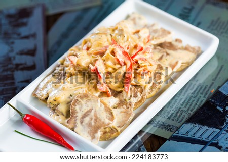 boiled beef tongue sliced on a plate with dill - stock photo
