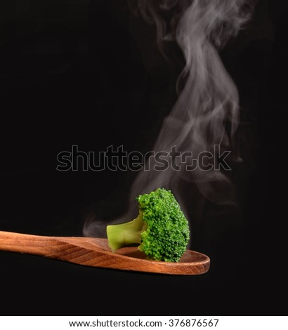 Boiled broccoli on wood spoon. - stock photo