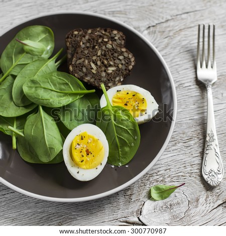 Boiled egg and fresh spinach on a brown plate on a light wooden background. Healthy Breakfast or snack - stock photo