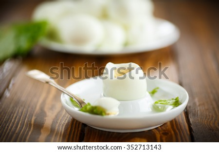 boiled egg with a spoon on the saucer - stock photo