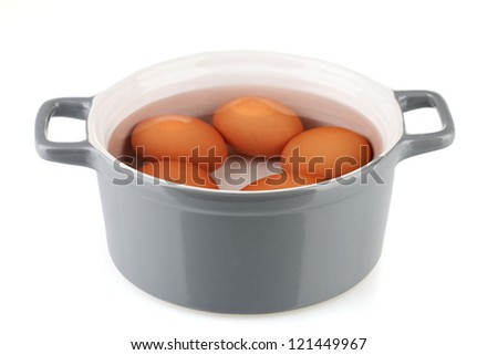 Boiled eggs in saucepan isolated on white - stock photo
