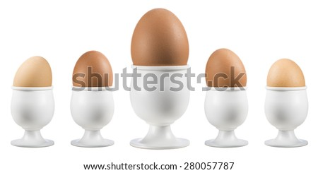 boiled eggs on eggcup in a row on white background - stock photo