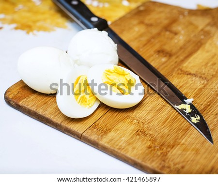Boiled eggs over wooden background, knife and eggs on a cutting board, Closeup of knife cutting egg, sliced egg with knife, Fresh hard boiled eggs with shell beside - stock photo