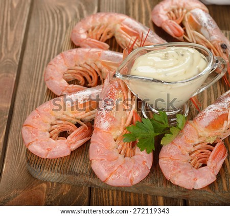 Boiled langoustines with sauce on a brown background - stock photo