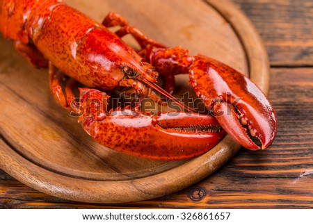Boiled lobster on wooden cutting board - stock photo