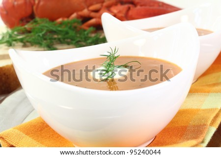 boiled lobster soup with lemon, dill and cream dollop - stock photo