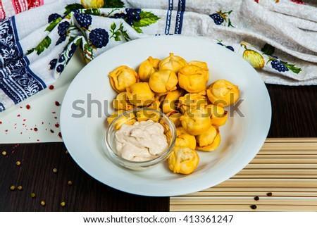 Boiled prepared homemade russian dumplings or pelmeni - stock photo