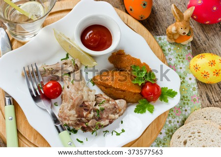 Boiled Rabbit with a garnish of vegetables and eggs with tomato sauce on a table decorated Easter - stock photo