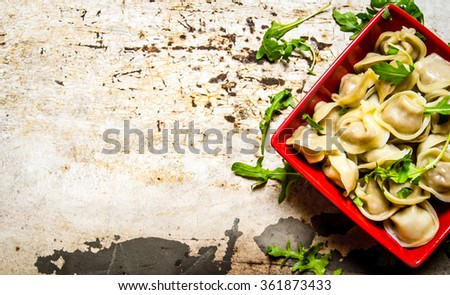Boiled ravioli with herbs and olive oil. On the rustic background. Free space for text . Top view - stock photo