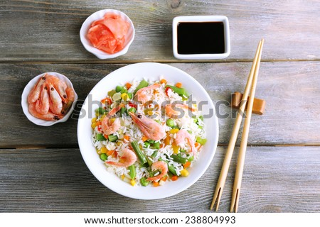 Boiled rice with shrimps and vegetables on wooden background - stock photo
