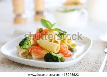 Boiled rigatoni pasta with salmon and broccoli on white plate - stock photo