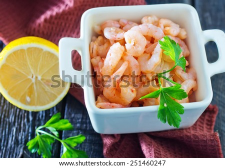 boiled shrimps and fresh lemon on a table - stock photo