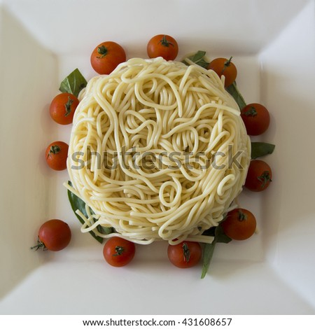 Boiled spaghetti garnished with cherry tomatoes and basil  - stock photo