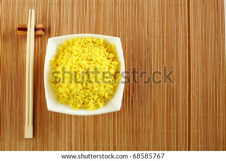 Boiled yellow rice and a white plate beside lie wooden sticks. Plate stands on a wooden mat - stock photo