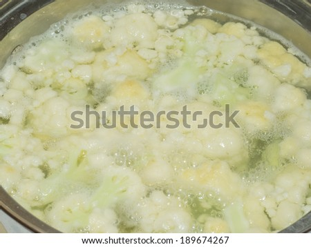 Boiling cauliflowers and potatos in large metal pot. - stock photo