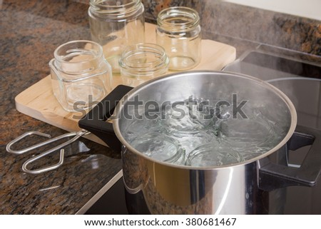 Boiling glass jars for sterilization and preparing homemade jam.  - stock photo