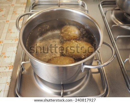 Boiling potatoes in a saucepot on a gas cooker - stock photo