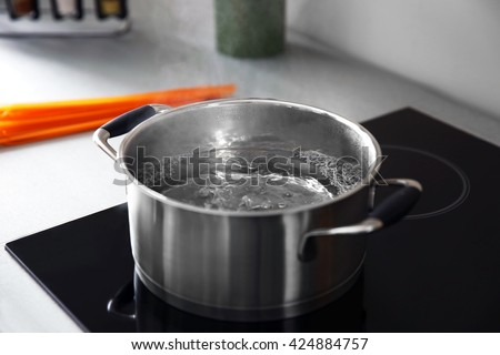 Boiling water in pan on electric stove in the kitchen - stock photo