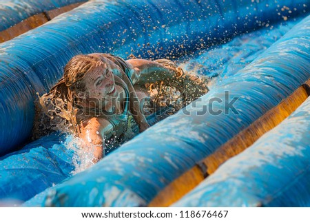 BOISE, IDAHO - AUGUST 25: Unidentified woman slides with a huge smile at the Dirty Dash August 25 2012 in Boise, Idaho - stock photo