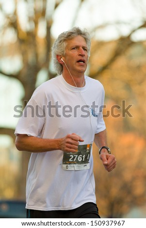 BOISE, IDAHO - NOVEMBER 22: Runner 2761 participating in the early morning run of The Turkey Day 5kin Boise, Idaho on November 22, 2012 while listening to music - stock photo