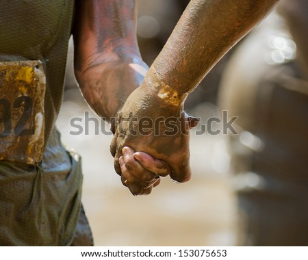 BOISE, IDAHO/USA - AUGUST 11: Couple hold hands while they work their way through the course at the The Dirty Dash in Boise, Idaho on August 11, 2013  - stock photo