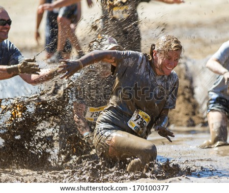BOISE, IDAHO/USA - AUGUST 10, 2013: Runner 7358 smiles as she is getting splashed at the The Dirty Dash - stock photo