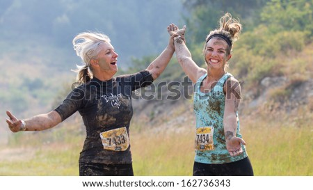 BOISE, IDAHO/USA - AUGUST 10: Two friends hold hands at the The Dirty Dash in Boise, Idaho on August 10, 2013  - stock photo
